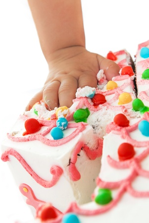 baby girl touching the birthday cake with her fingers photo