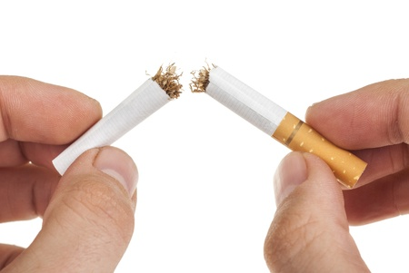 unhealthy living: breaking a cigarette. Isolated on a white background