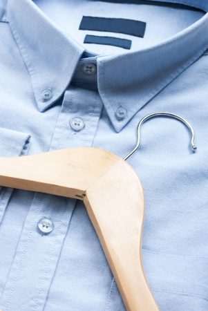 dry cleaned: Wooden cloth hanger on top of blue shirt