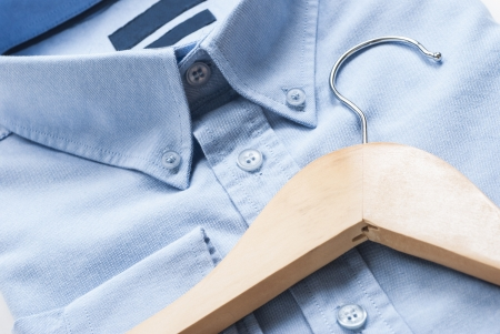 dry cleaner: Wooden cloth hanger on top of blue shirt