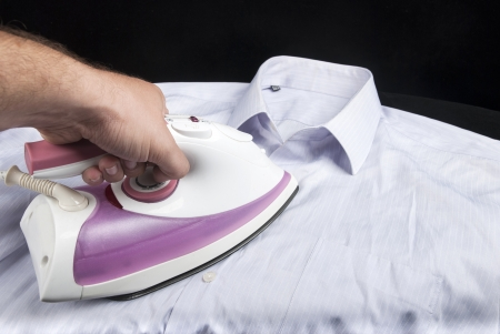 domestic task: ironing shirt with Hot steam iron on black background Stock Photo