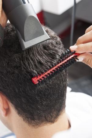 peluquero: Barber secar el cabello con secador de pelo en una peluquer�a