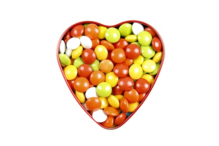 Multicolor candies in heart shape candy box on white background photo