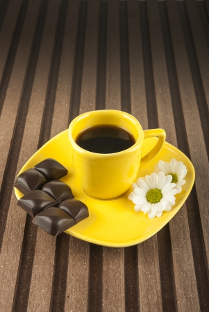 Yellow cup and pieces of dark chocolate on wooden background photo