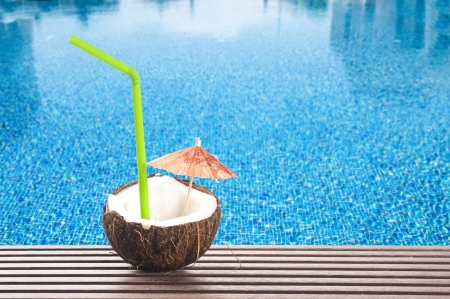 coconut cocktail with green drinking straw and cocktail umbrella by the swimming pool