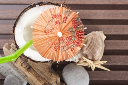 coconut coktail with green drinking straw and coktail umbrella pebbles, seastar, seashell photo