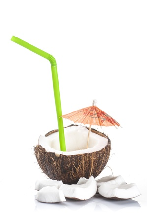 caribbean drink: coconut cocktail with green drinking straw and cocktail umbrella on white background