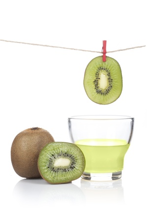 kiwi hung on rope with clothes peg and glass of kiwi juice on white background photo