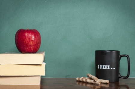 teaching material: books coffee mug wafer rolls and apple in front of green chalkboard Stock Photo