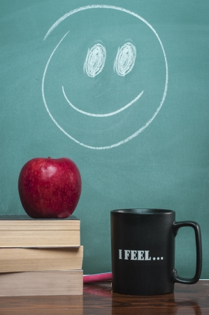 teaching material: books coffee mug and apple in front of green chalkboard