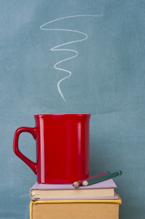 books coffee mug and pencil in front of green chalkboard photo