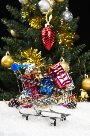 new year gift boxes in shopping cart on snow photo