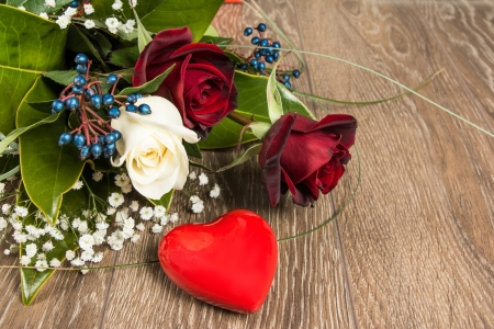 Red and white roses bouquet isolated on the wooden  photo