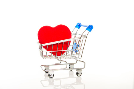 big red heart in shopping cart on white background photo