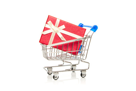 red gift box in steel shopping cart on white background photo