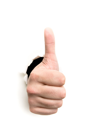 Thumbs up through the paper hole isolated on white background photo