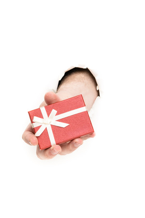 hand holding red gift box through the paper hole isolated on white background photo