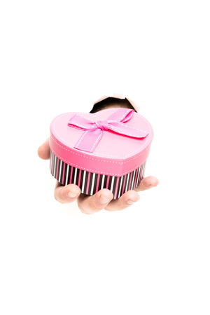 hand holding pink gift box through the paper hole isolated on white background photo