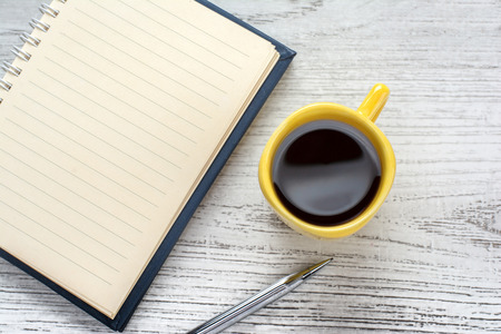 blank notebook coffee cup and notebook on wooden background photo