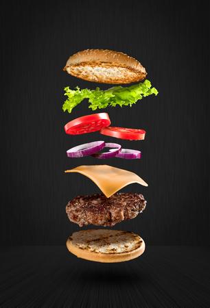 Hamburger délicieux avec des ingrédients volants sur fond noir Banque d'images - 91552261