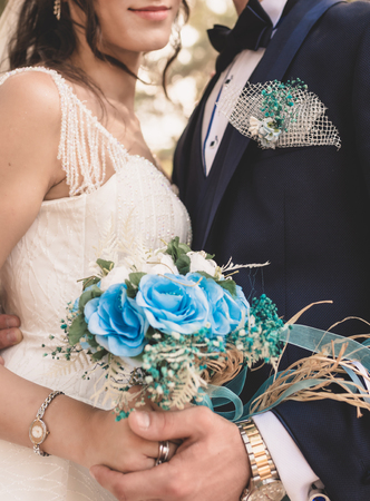 hand of bride holding bouquet of blue flowers