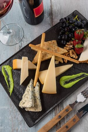 Cheese plate served with grapes, strawberry, crackers and nuts on a wooden background