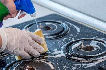 Cleaning a gas stove with kitchen utensils, household concepts, or hygiene and cleaning. Foto de archivo - 134567178