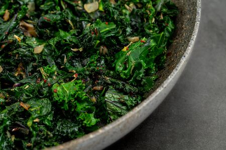 sauteed kale with onion in a pan with olive oil, healthy cooking concept