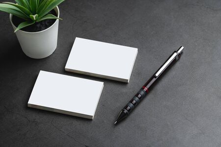 Empty business cards and pencil. Mockup for branding identity on dark stone background