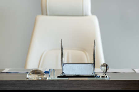 Silver name holder and pen holder on office table Standard-Bild