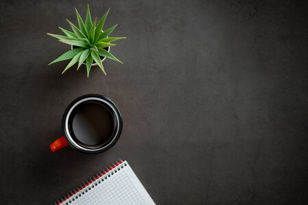 table top view with notepad, coffee and plant on black background. Banque d'images