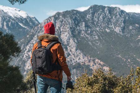 Jeune photographe masculin de race blanche au sommet d'une montagne par temps clair.