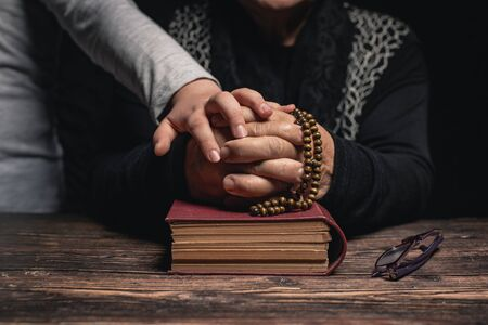 Girl and Old Woman with closed hands holding rosary on holy book staying at home and praying for protection ageainst coronavirus covid-19 pandemi concept.