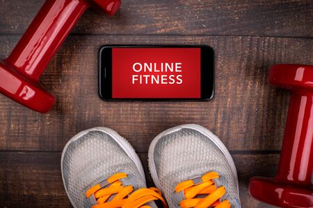 Gray sneakers, red dumbbell and smartphone on a woodan background. App for training indoors. Online Fitness program. Home online workout. Top view, Covid-19 Coronavirus quarantine concept