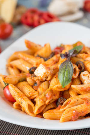 Penne pasta in tomato sauce with chicken, tomatoes decorated with parsley