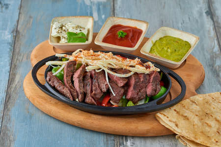 Beef Fajitas with colorful bell peppers in pan and sauces Stock Photo