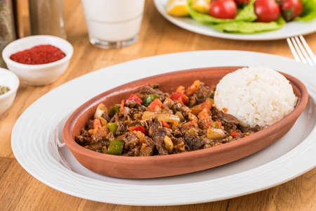 Turkish meat casserole and rice on wooden table.