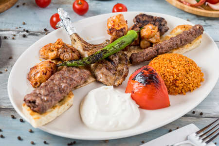Mixed grill on wooden table. Lamb chops, Adana kebab, chicken shish, shish meatballs, steak.