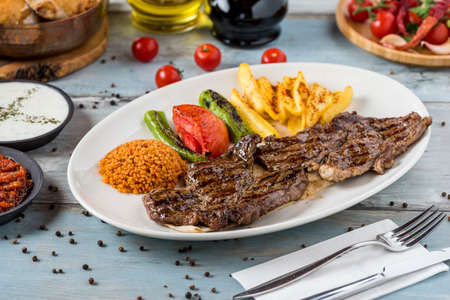 Grilled steak on wooden table. with bulgur pilaf, french fries, tomatoes garnish.
