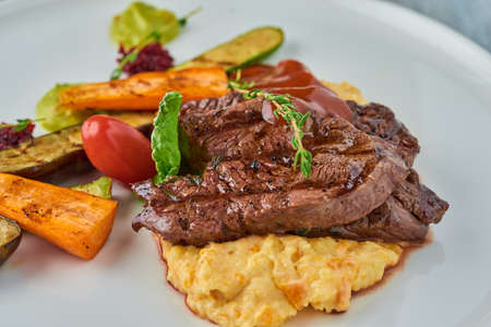 Grilled steak on mashed potatoes with grilled vegetables.