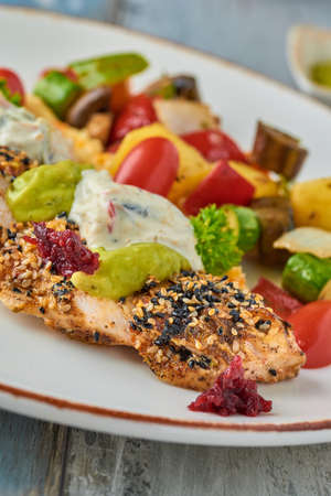 grilled chicken with sesame next to grilled vegetables on wooden table Stock fotó