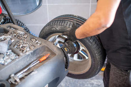 worker balancing tire with wheel balancing machinery in workshop