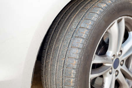 Close up of dirty car wheel with rubber covered rubber tire. Banque d'images