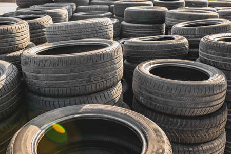 Old and worn car tires stacked on top of each other.
