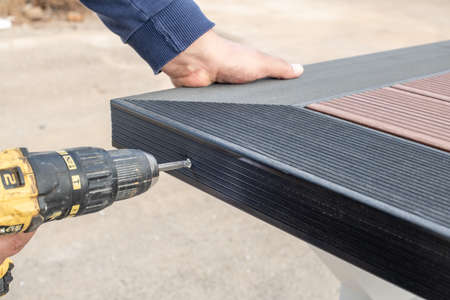 The guy assembling the composite deck table with a cordless screwdriver.