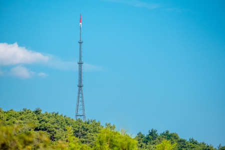 Telecommunication tower with signal amplifiers for mobile communications and antennas is installed in a rural area on a grassy field with trees. Stock Photo