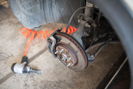 Car without wheel and lift up by hydraulic, waiting for tire replacement. Banque d'images