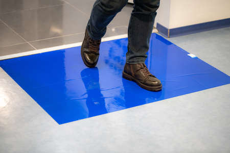 Man in brown shoes stepping on blue Adhesive Sticky Mats.