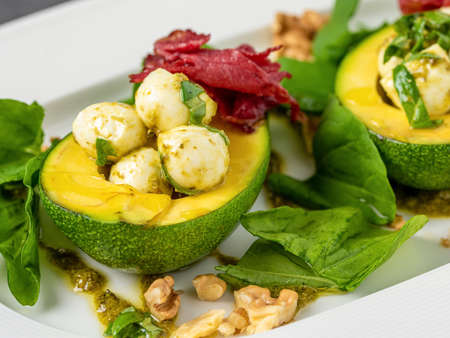 Bocconcini cheese balls in halves of avocado served with salad on white plate