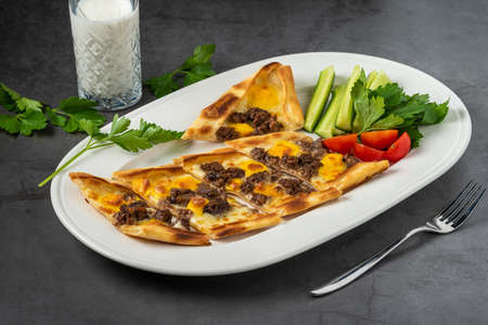 Sliced cubed meat pita with buttermilk and salad on stone table.